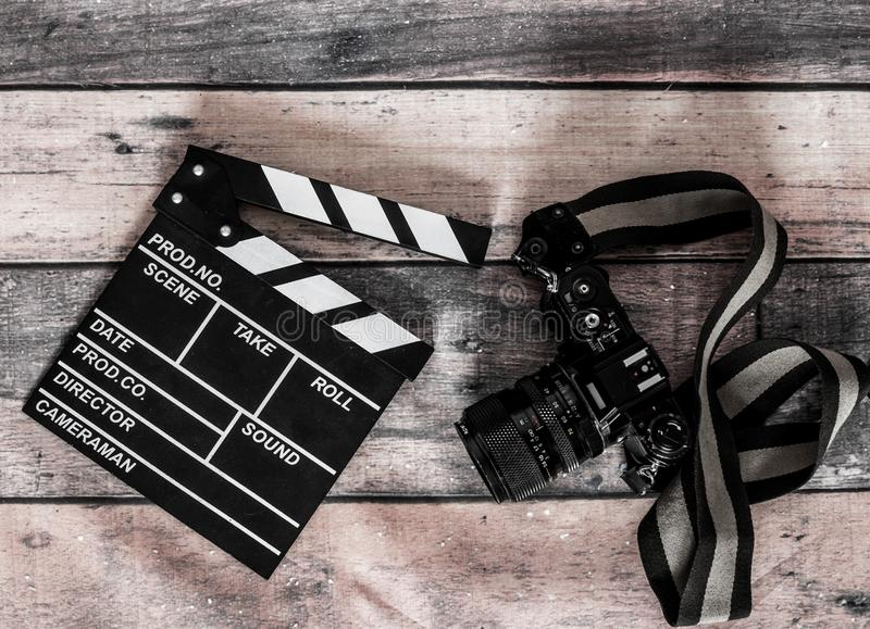 Movie clapper and old camera on a wooden background, movie shoot stock image