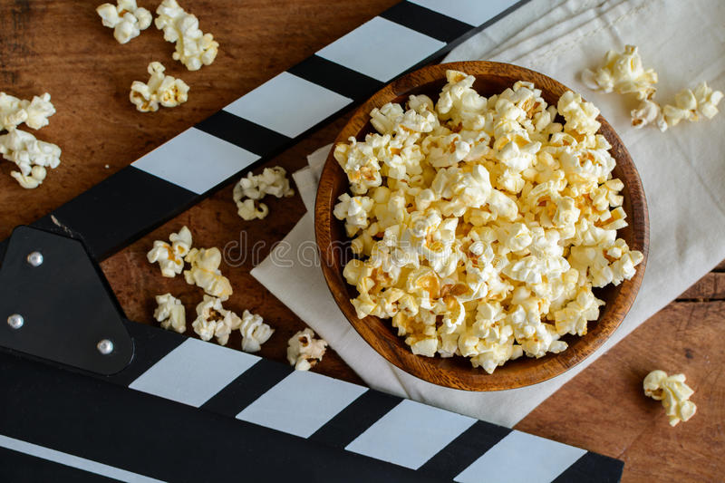 Movie clapper with popcorn. Movie clapper and popcorn on wooden background royalty free stock images