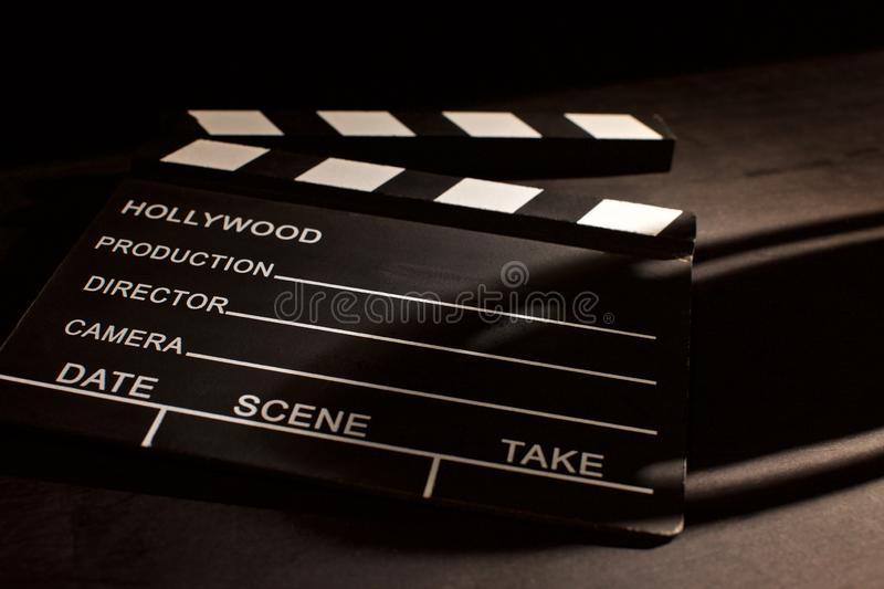 Movie clapper with shadow on wooden black background stock photography