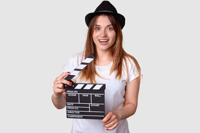 Movie concept. Positive young woman in hedgear holds cinema clapper, dressed in casual t shirt, has pleased expression, isolated stock image