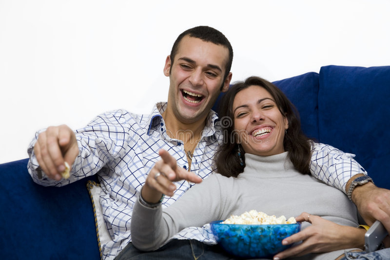Movie night. Young couple watching tv at home and laughing