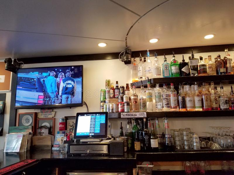 Movie plays on TV inside Local Downbeat Diner Bar. Honolulu - August 6, 2017: Movie plays on TV inside Local Downbeat Diner Bar with liquor on display and cash stock photo