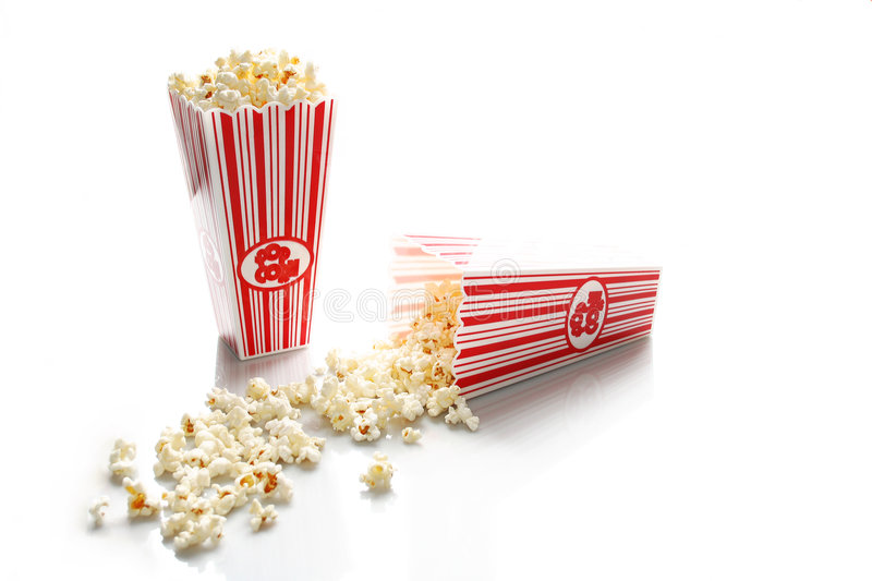 Movie Popcorn. Two red and white striped containers of movie popcorn, one standing upright and the other spilled on it's side. Isolated on a white background stock images