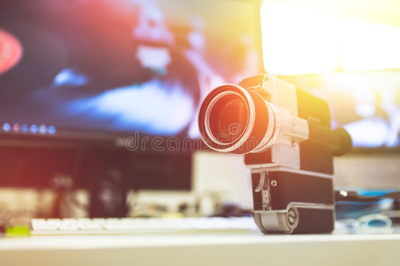 Movie production: vintage old movie camera on a desk, cutting room in the background. Sunshine stock photos