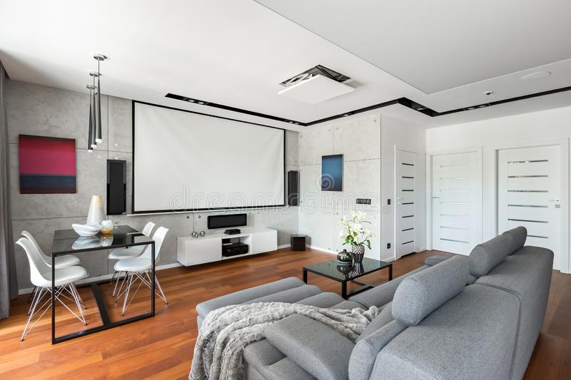 Movie room with projector screen. Modern movie room with projector screen, gray sofa, black table and white chairs stock photo