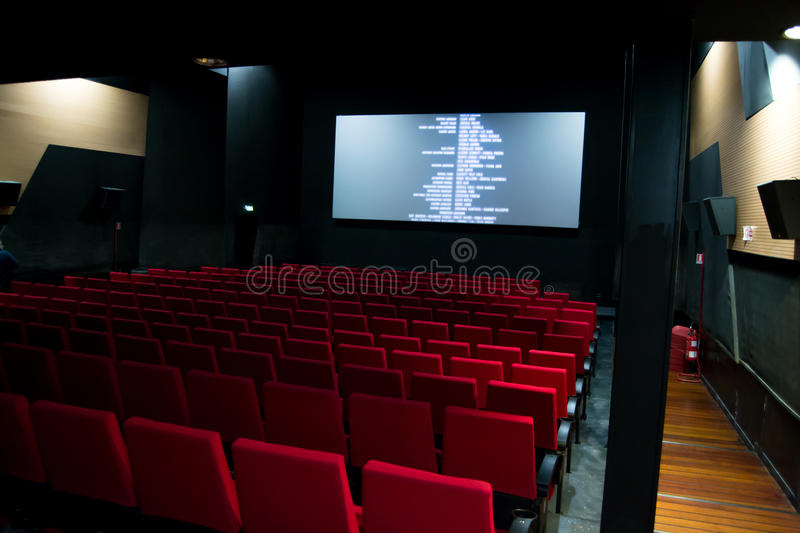 Movie screen and red chairs inside of a cinema.  royalty free stock images