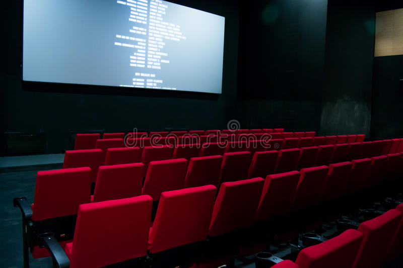 Movie screen and red chairs inside of a cinema.  royalty free stock image