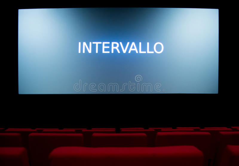 Movie screen and red chairs inside of a cinema. Movie screen with the sign break in Italian language and red chairs inside of a cinema stock images