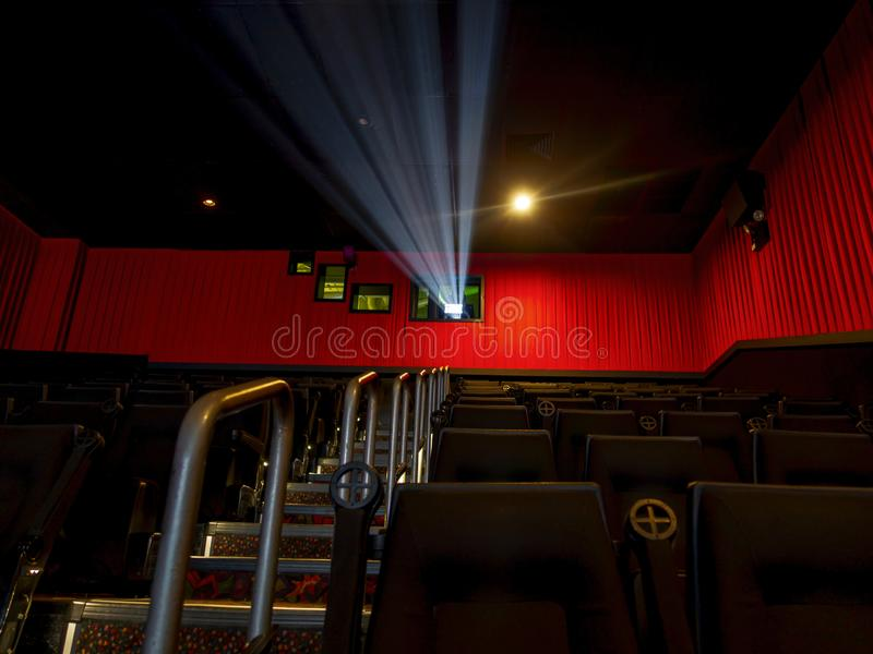 Movie silver screening room theater with projector light on and seating and stairs on lush red color curtains royalty free stock photography