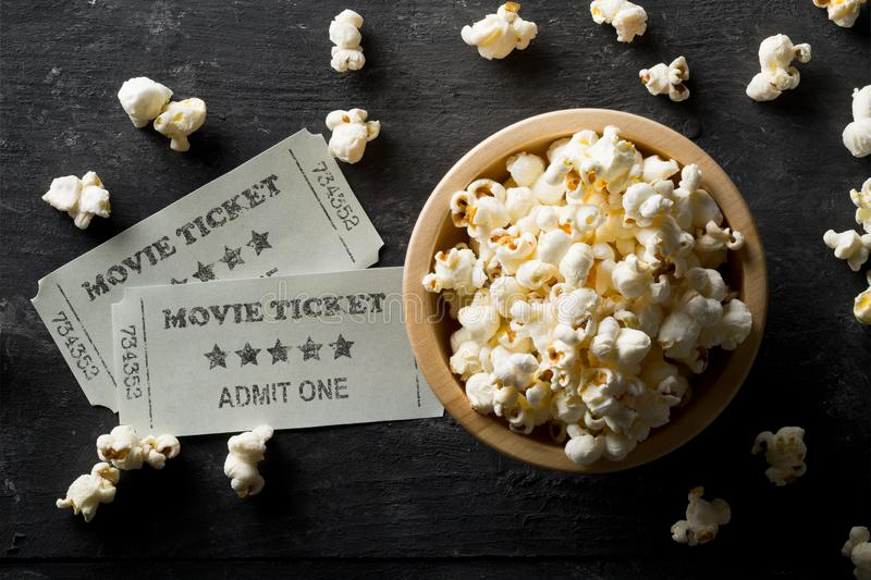 Movie tickets and bowl of popcorn on dark background. Home theatre movie or series night concept. Flat lay top view from above.  royalty free stock photos