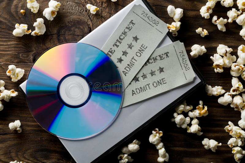 Movie tickets, DVD or blu ray disc and popcorn on dark wooden table background. Home theatre movie or series night concept. Flat. Lay top view from above royalty free stock photography