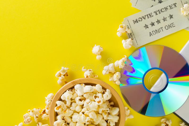 Movie tickets, DVD or blu ray disc and popcorn on yellow table background. Home theatre movie or series night concept. Flat lay. Top view from above with copy royalty free stock photos