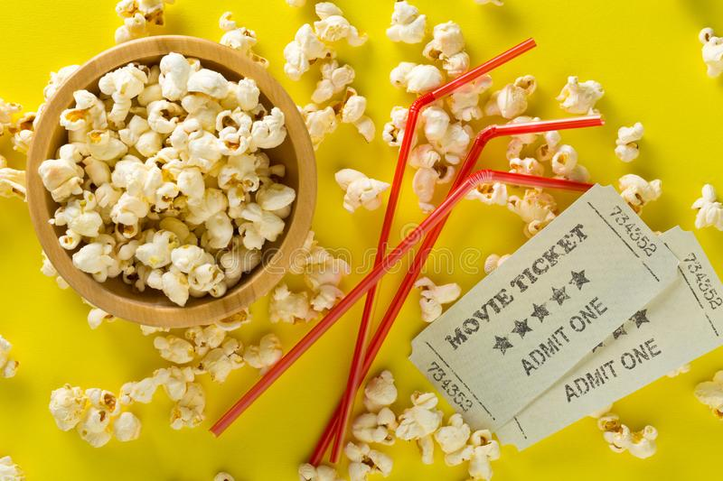 Movie tickets, soda drink plastic straws and popcorn on yellow table background. Home theatre movie or series night concept. Flat. Lay top view from above stock photography