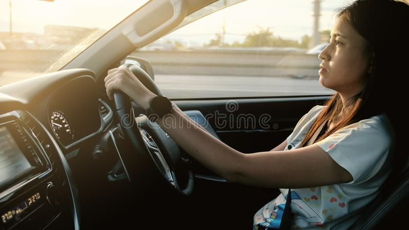 Movimentação da mulher um carro moderno na estrada imagem de stock