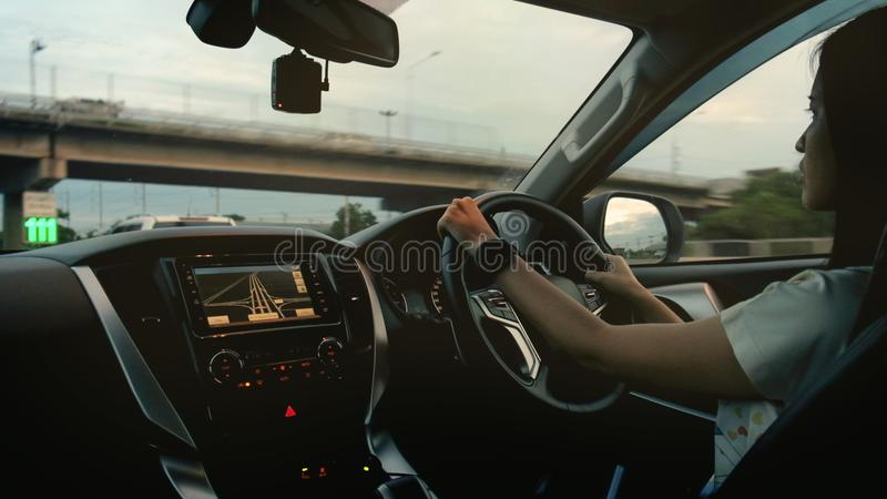 Movimentação da mulher um carro moderno na estrada foto de stock