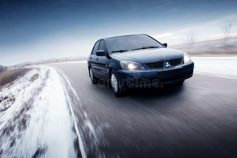 Movimentação de Mitsubishi Lancer do carro na estrada do campo do asfalto no dia do inverno imagem de stock