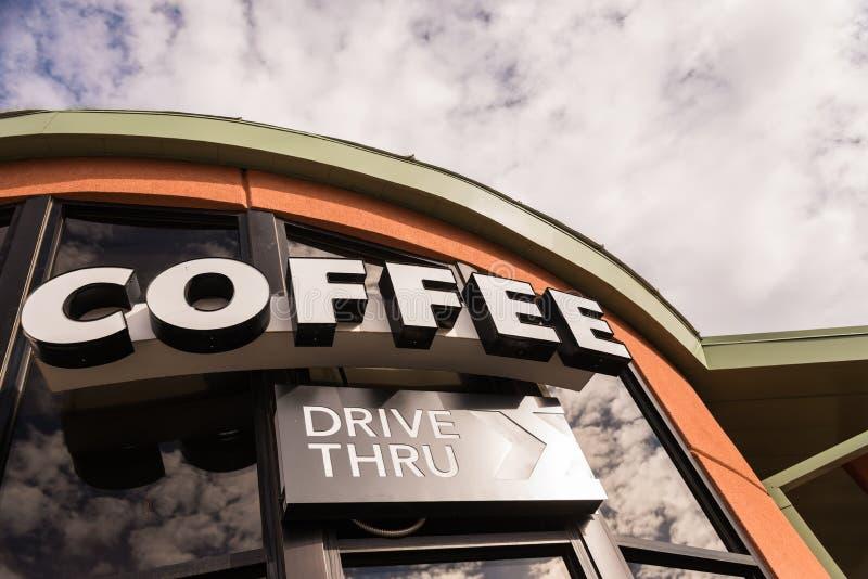 Movimentação do café através do sinal com céu nebuloso imagens de stock
