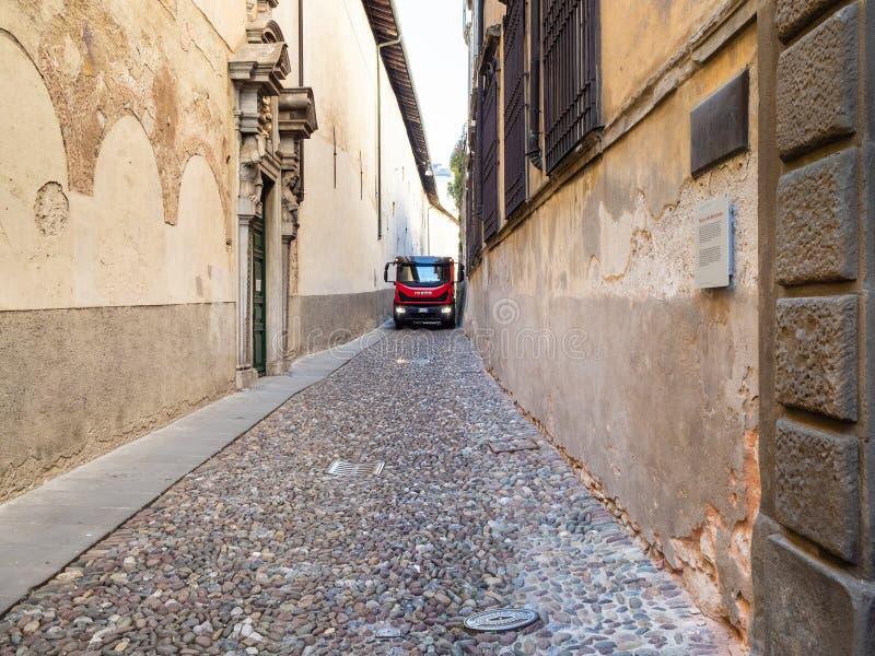Movimentação do caminhão na rua medieval estreita em Bergamo foto de stock