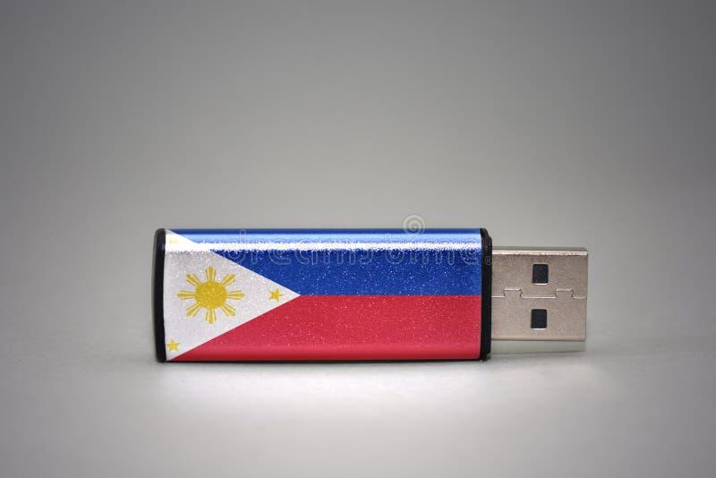 Movimentação do flash do Usb com a bandeira nacional de Filipinas no fundo cinzento fotos de stock royalty free