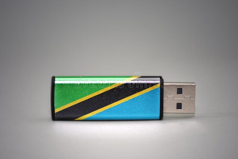 Movimentação do flash do Usb com a bandeira nacional de Tanzânia no fundo cinzento foto de stock