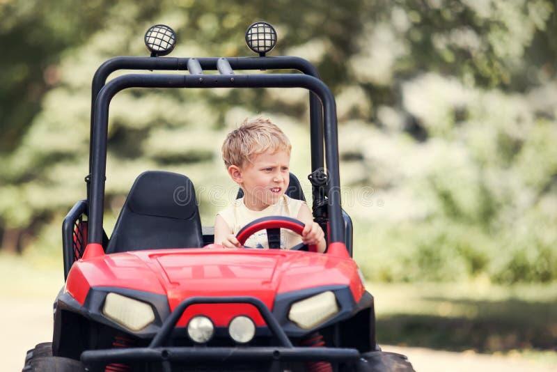 Movimentação do rapaz pequeno um mini carro bonde no parque imagem de stock royalty free