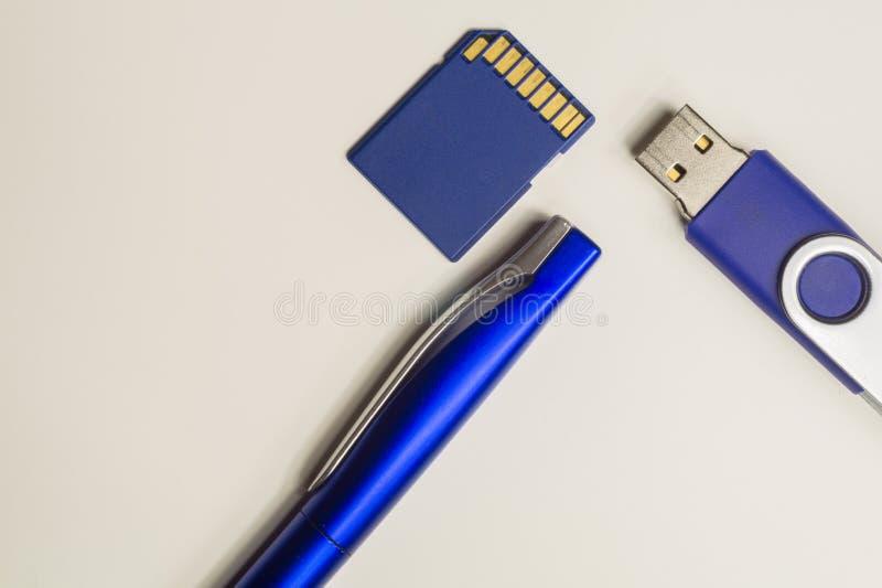 Movimentação do Usb e cartão de memória instantâneos com a pena azul Isolado no fundo branco Copie o espaço fotografia de stock royalty free