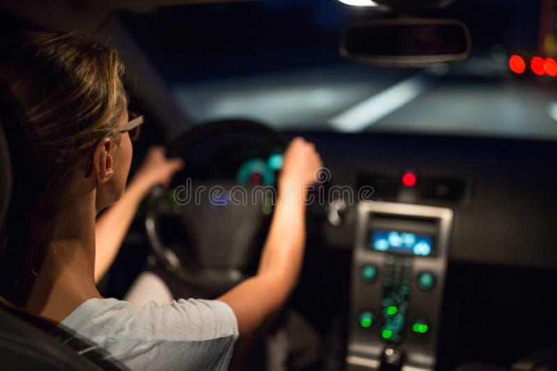 Movimentação fêmea que conduz um carro na noite imagens de stock royalty free