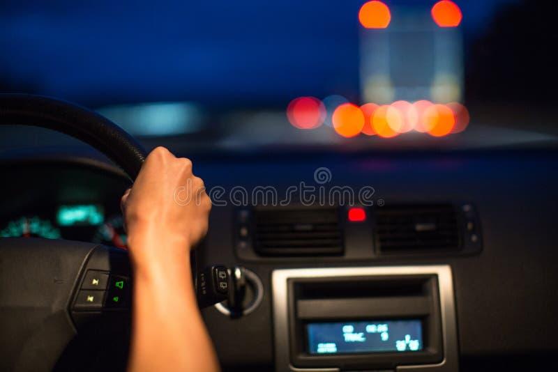Movimentação fêmea que conduz um carro na noite imagem de stock