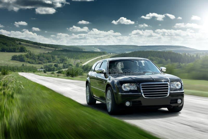 A movimentação preta da velocidade do carro jejua na estrada asfaltada no dia imagens de stock