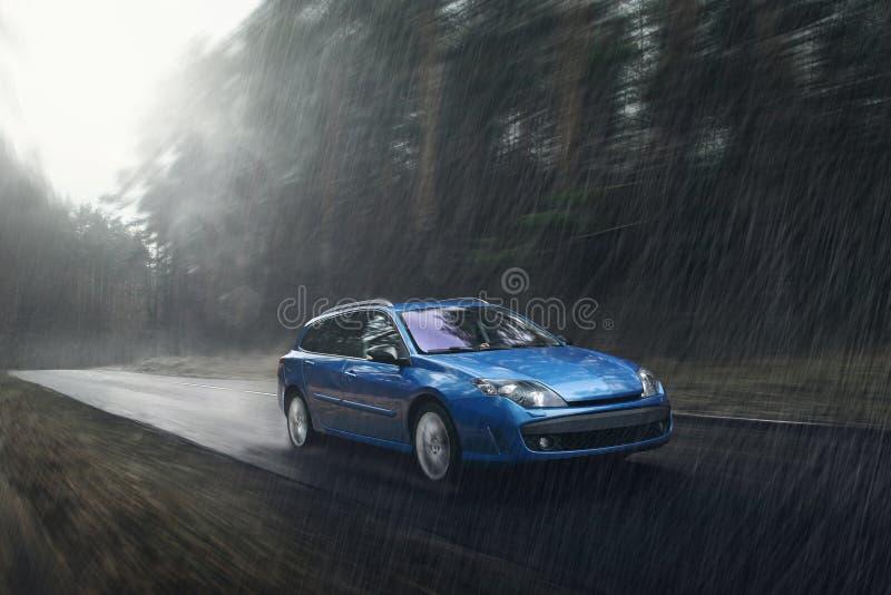 Movimentação rápida do carro azul na estrada molhada na chuva no dia fotografia de stock