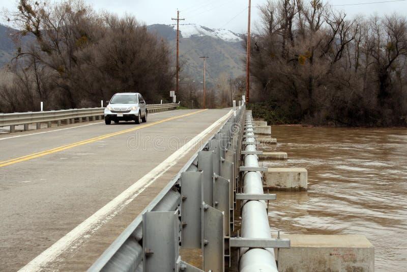 Movimentações do carro sobre a ponte durante a inundação foto de stock royalty free
