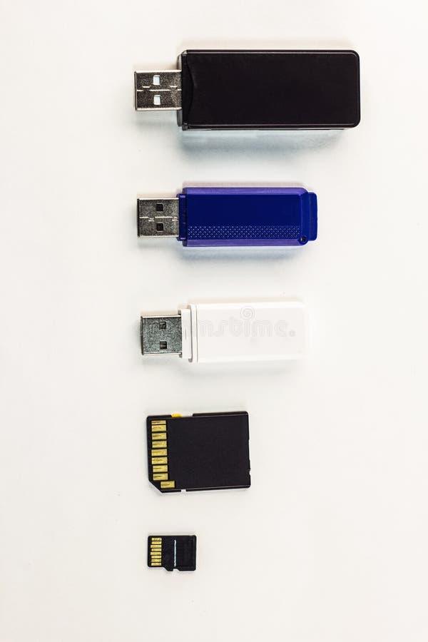Movimentações do flash do Usb de tamanhos diferentes em um fundo branco, compactas imagens de stock