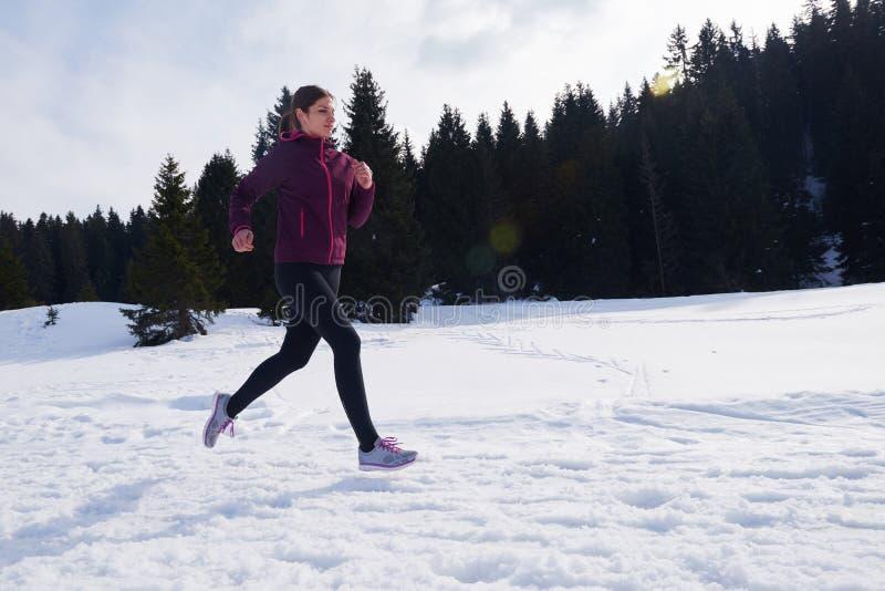 Movimentar-se da mulher de Yougn exterior na neve na floresta imagem de stock