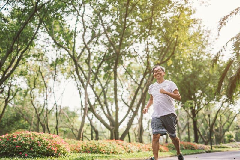 Movimentar-se de corrida do homem maduro superior asiático no parque imagem de stock