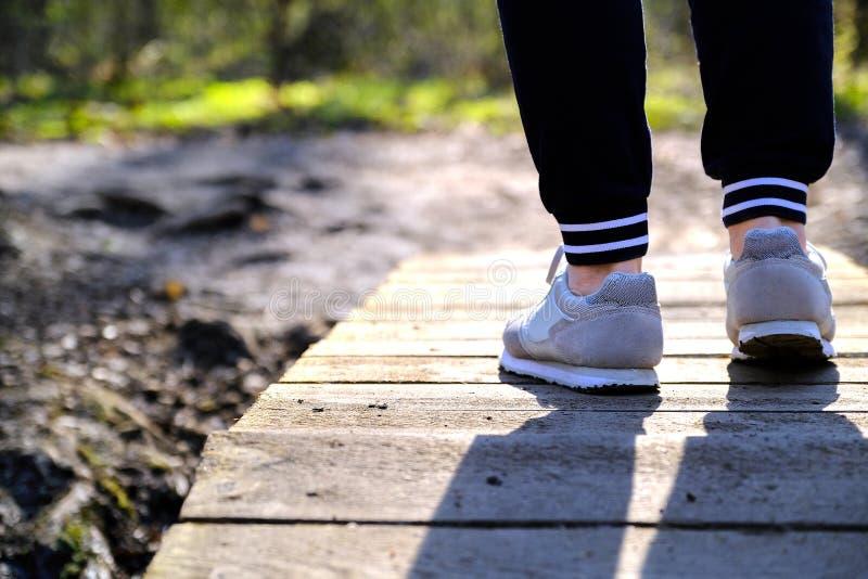 Movimentar-se nas sapatilhas na ponte no parque Esporte, sa?de e conceito f?sico da cultura foto de stock