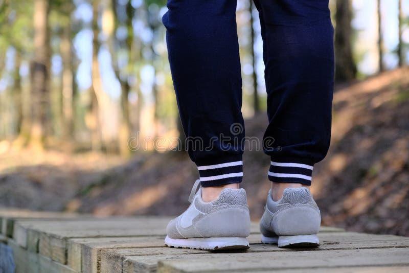 Movimentar-se nas sapatilhas na ponte no parque Esporte, sa?de e conceito f?sico da cultura imagens de stock royalty free
