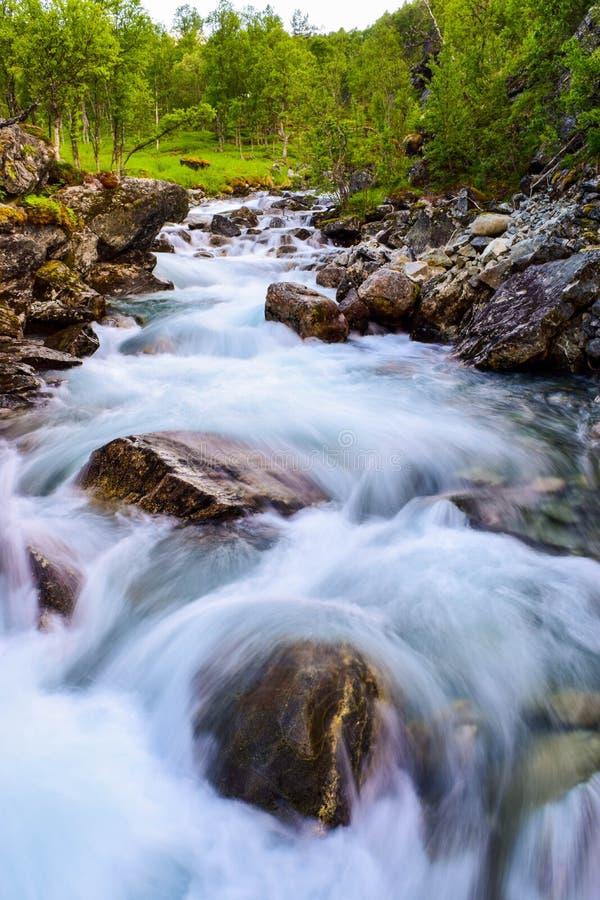 Movimenti sfocati acqua del fiume Fiume  lungo le montagne di Aurlandsfjellet in Norvegia immagini stock libere da diritti