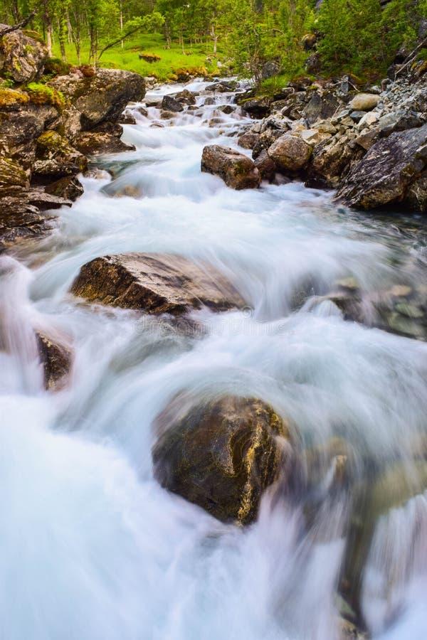 Movimenti sfocati acqua del fiume Fiume  lungo le montagne di Aurlandsfjellet in Norvegia immagini stock