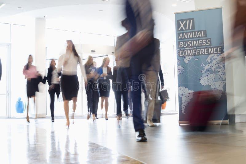 Movimento borrado dos executivos que andam no centro de convenções fotografia de stock royalty free