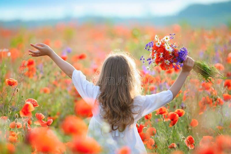 Movimento della ragazza del bambino attraverso il campo di fioritura con i fiori selvaggi rossi fotografia stock