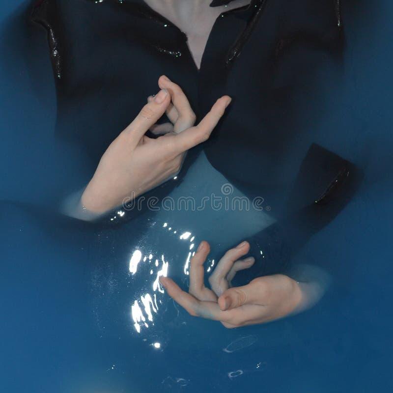 Movimento delle mani in un cerchio in acqua blu immagine stock libera da diritti
