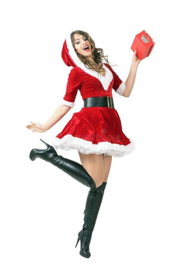 Movimento do meio do ar de saltar a mulher entusiasmado de Santa que guarda a caixa de presente fotos de stock