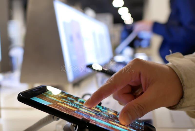 Movimento dos povos que jogam no telefone celular da galáxia S8 de Samsung dentro da loja eletrônica imagens de stock