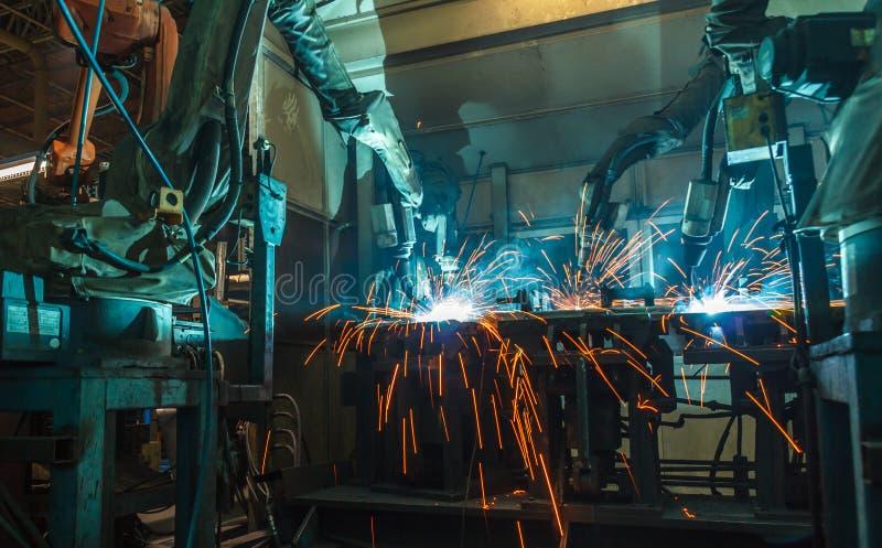 Movimento dos robôs de Team Welding em uma fábrica do carro fotografia de stock royalty free