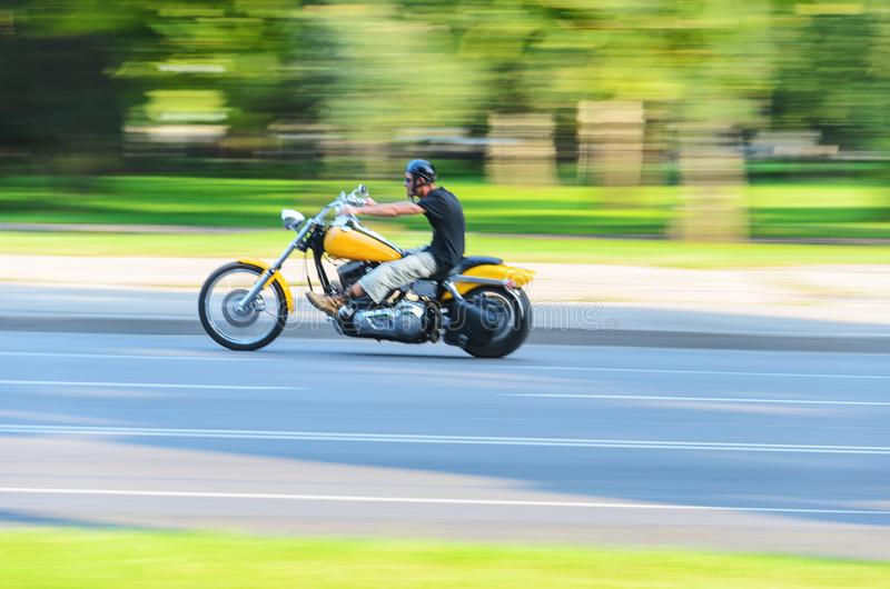 Movimento lento astratto, motociclista che guida motocicletta gialla fotografie stock