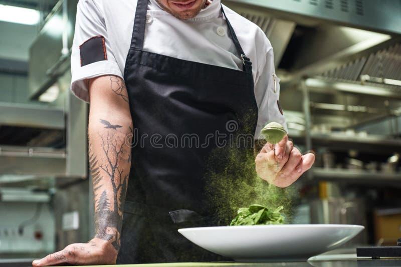 Movimento lento Imagem colhida das mãos do cozinheiro chefe com as tatuagens que adicionam especiarias na salada ao estar em uma  fotografia de stock