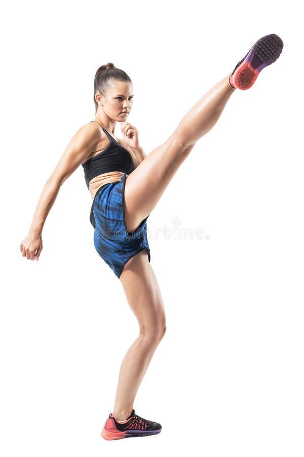 Movimento parado da ação do lutador kickboxing da mulher resistente que faz o pontapé alto imagens de stock royalty free