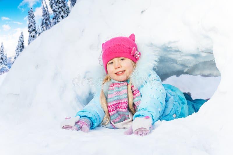 Movimento strisciante della bambina tramite il tunnel della neve in parco fotografia stock