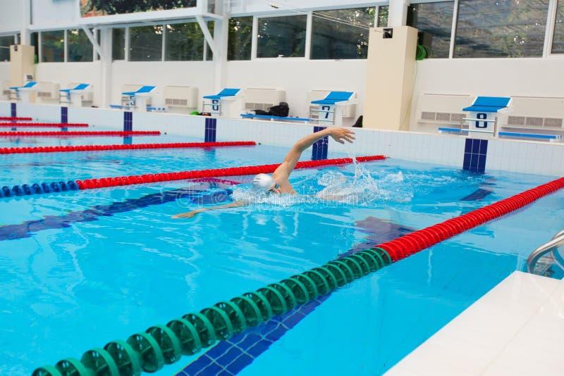 Movimento strisciante di nuoto del nuotatore dell'uomo in acqua blu immagini stock libere da diritti