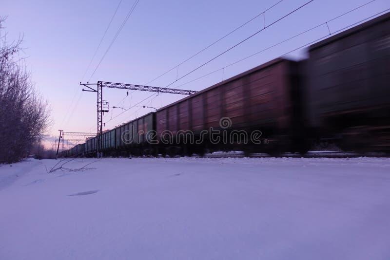 Movimentos do trem de mercadorias na alta velocidade no inverno após a queda de neve pesada Borrão de movimento parcialmente leve imagem de stock royalty free